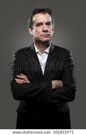 Grumpy Stern Middle Age Business Man in Suit Arms Folded Grey Background High Contrast Grunge Look - stock photo