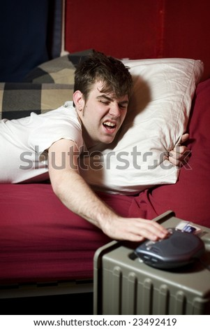 Grumpy young man waking up and turning his alarm clock off - stock photo