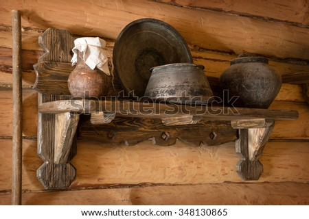 Grunge aged country style storage shelving rack in timber barn with pewter saucepan, copper plate, jam in clay crock knotted canvas. Closeup view with space for text on brown bar wall cottage backdrop - stock photo