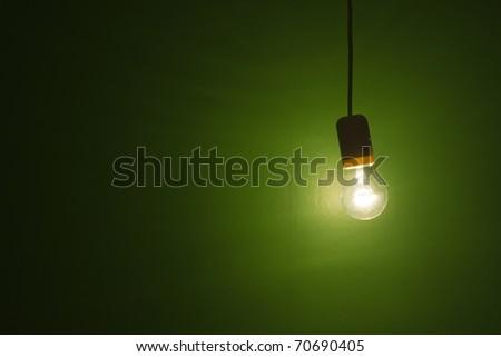 grunge background lightbulb shinning and hanging against green background
