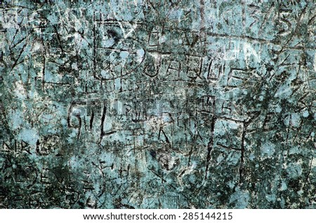 Grunge background of graffiti and sayings carved on a blue wall - stock photo