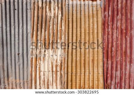 Grunge background of weathered corrugated iron fence panels - stock photo