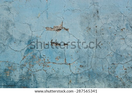 Grunge Background. Wall with the blue whitewash falling off fragment with cracks as a background texture - stock photo