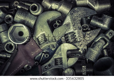 Grunge background with wet tools and bolts. Adjustable wrench, screws, nuts. Toned. - stock photo