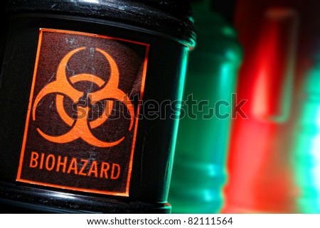 Grunge biohazard universal symbol danger warning label on a dangerous toxic waste black container in a scary hazardous material disposal site - stock photo