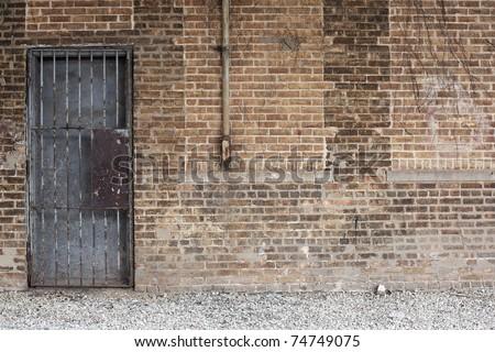 grunge brick wall & barred door - stock photo