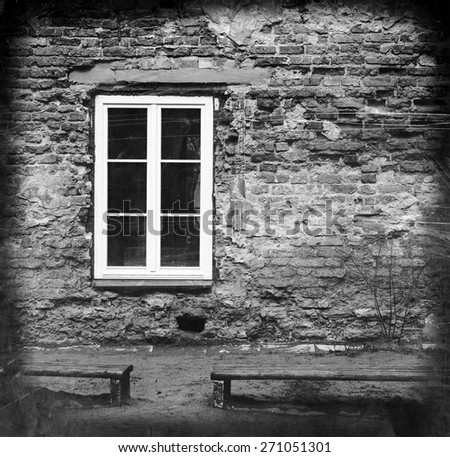 grunge brick wall with a window and two benches, black and white image - stock photo