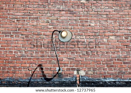 Grunge brick wall with curved lamp fixture turned on - stock photo