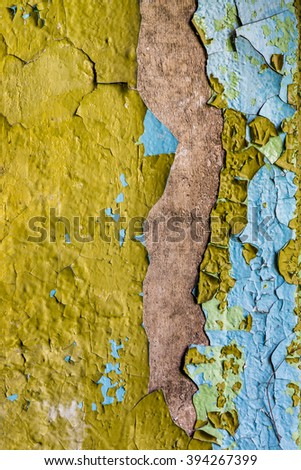 Grunge concrete wall with yellow peeling paint texture
