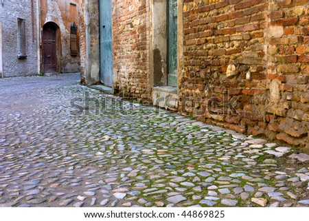grunge dark alley, slums of the city, squalid dirty corner of street, the decadent old town, pavement of porphyry cobblestones - stock photo