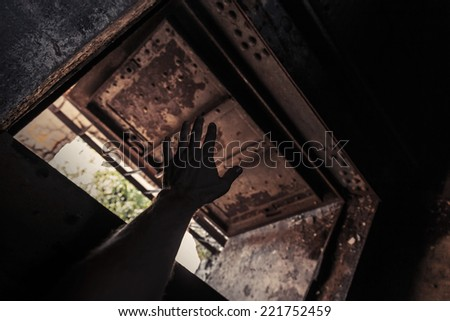 Grunge dark interior with open rusted door and male hand silhouette - stock photo