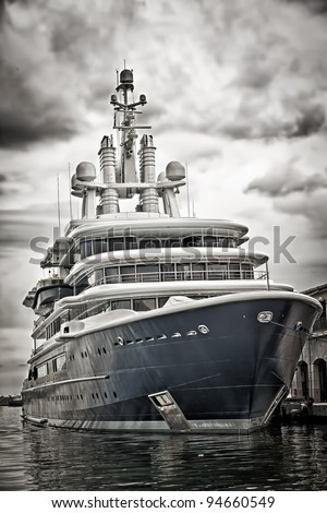Grunge desaturated view of a modern scientific research or tourism ship docked in a pier with a violent storm approaching - stock photo