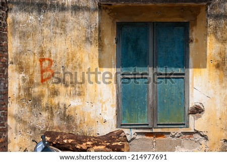 grunge green window on yellow wall - stock photo