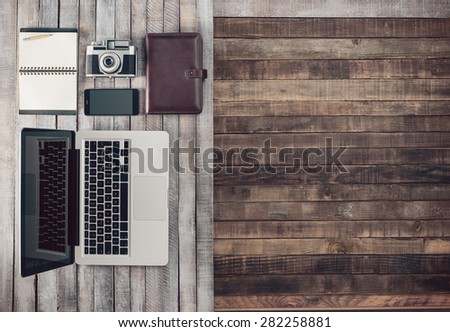 Grunge hipster wooden desktop with vintage camera, computer, mobile phone and notebook, blank copy space - stock photo