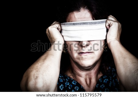 Grunge image of a serious woman with a handkerchief covering her eyes to avoid seeing isolated on black (useful to illustrate gender discrimination or prejudices) - stock photo