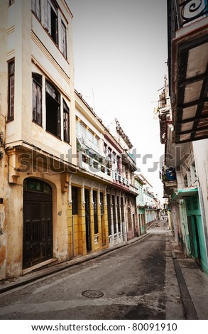Grunge image of a street in Old Havana sidelined by colorful crumbling buildings - stock photo
