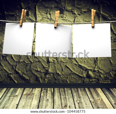 grunge interior, cracked wall wooden floor and white papers attach to rope with clothes pins - stock photo