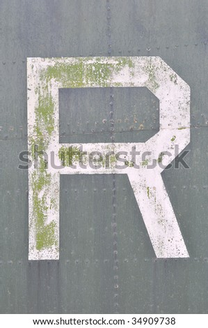 Grunge letter R painted on old metal surface with rivets - stock photo