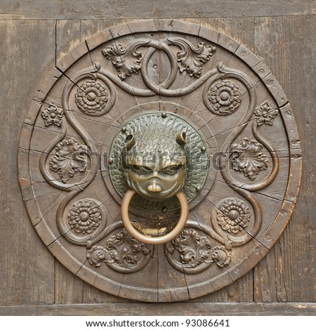 Grunge medieval background - rusty antique door knocker - stock photo