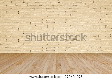 Grunge old aged brick wall painted in light yellow cream beige color tone with wooden floor textured background in light natural yellow brown color tone for interior backgrounds       - stock photo