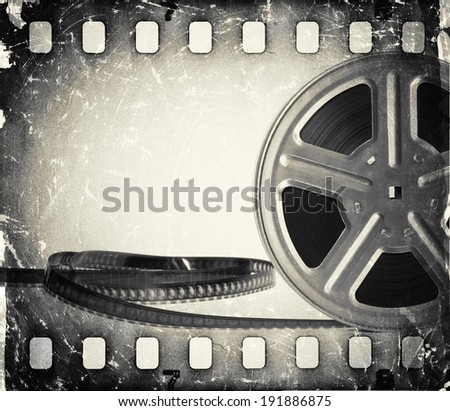 Grunge old motion picture film reel with film strip. Vintage background - stock photo