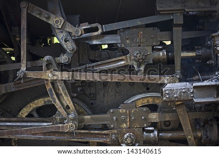 Grunge old steam locomotive wheel and rods - stock photo