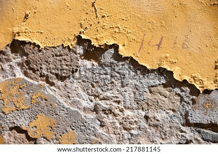 Grunge painted cement wall background texture with weathered damaged pitted concrete and peeling plaster and ochre colored paint - stock photo