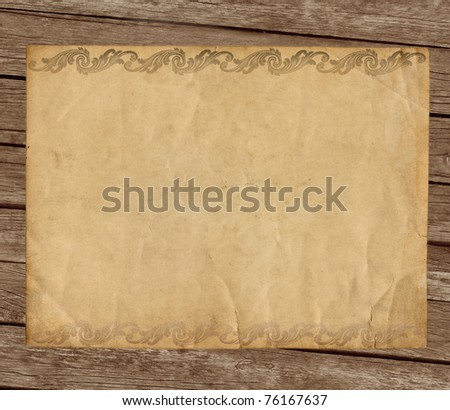 Grunge paper with ornament on wooden background - stock photo
