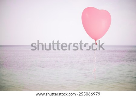 Grunge pink balloon over sea sky background with retro filter effect - stock photo