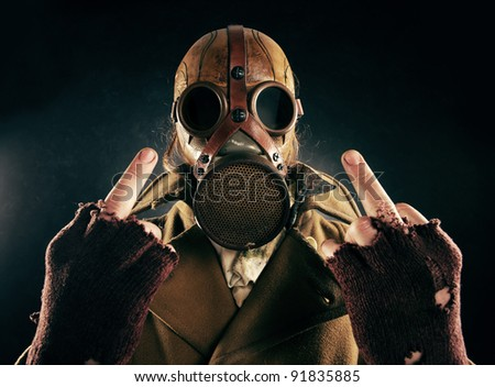 grunge portrait man in gas mask, fuck sign - stock photo