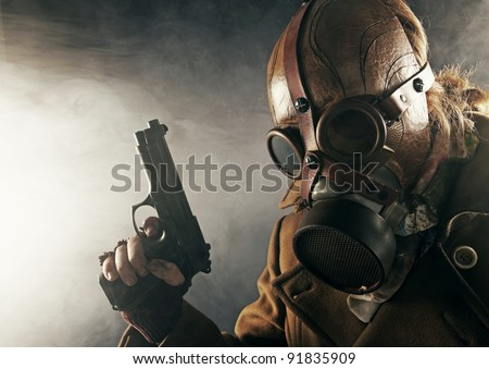 grunge portrait man with gun in gas mask