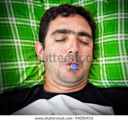 Grunge portrait of a sick hispanic man laying in bed with a thermometer in his mouth