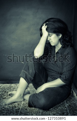 Grunge portrait of a very depressed woman sitting on the floor - stock photo