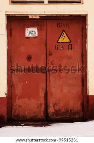 grunge rusty orange door, danger high voltage keep out in russian - stock photo