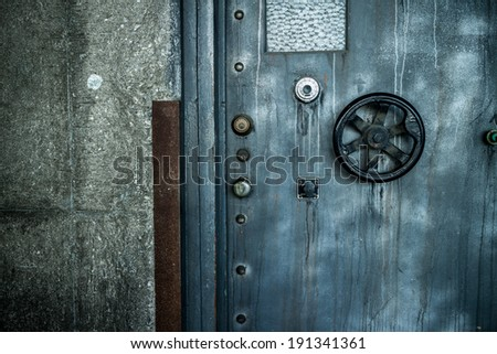 Grunge style image of old metal door background with vault lock. - stock photo