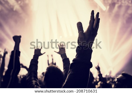 Grunge style photo of silhouette of people hands raised up on musical concert, enjoying music, dance club, active night life concept - stock photo