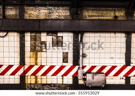 Grunge subway wall backdrop with broken tiles and caution lines - stock photo