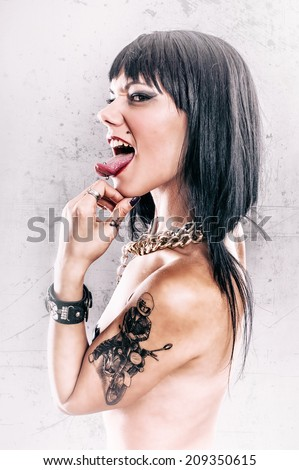 Grunge Tattoo Girl with Tongue Piercing. Aggressive and sexy tattoo lady with tongue piercing. Studio shoot.   - stock photo