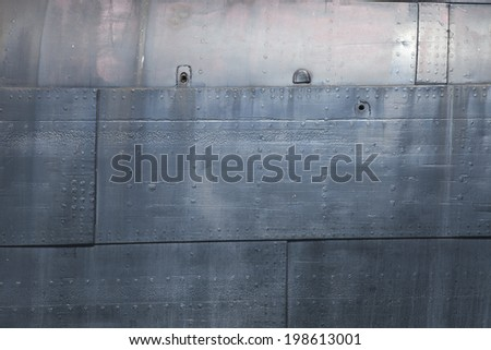 Grunge texture of plates and rivets on the side of an old ship - stock photo
