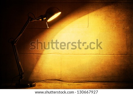 grunge textured picture of a desk lamp shining on a dark wall