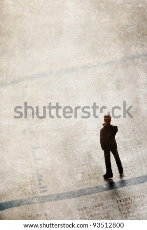 grunge textured picture with a businessman figurine standing upon a financial sector of a newspaper - stock photo