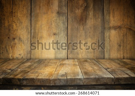 Grunge vintage wooden board table in front of old wooden background. Ready for product display montages  - stock photo