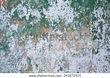Grunge wall texture background.  Paint cracking off dark wall with rust underneath. - stock photo