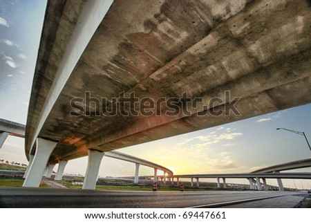 Grunge weathered texture under a freeway overpass at sunset - stock photo