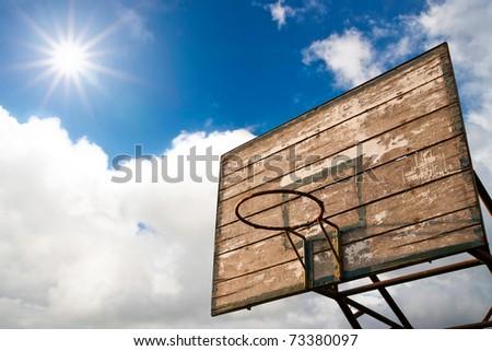 Grunge wooden basket hoop against sunrise on cloud blue sky - stock photo