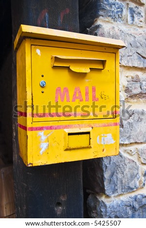 Grunge yellow mailbox old and empty in a portal. - stock photo
