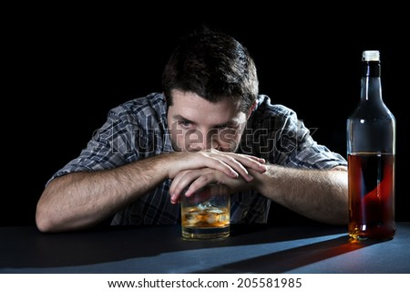 grunge young alcoholic man drunk at the table of a bar looking wasted and depressed with hands on whiskey glass isolated black background representing alcohol abuse, addiction and alcoholism concept