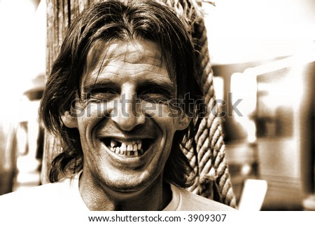 Grungey looking man in his 40's with some missing teeth but smiling happily - stock photo