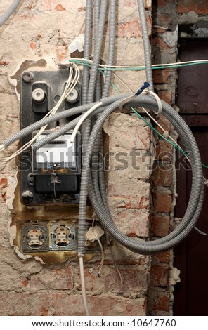 Grungy active energy meter with lots of power cables - stock photo
