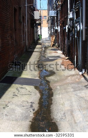 Grungy alley way behind various business with utillitie systems
